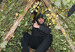 just-for-fun-adult-man-sat-inside-a-natural-shelter-he-has-made