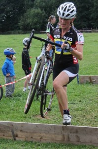 Cyclo cross woman carrying bike over obstacle